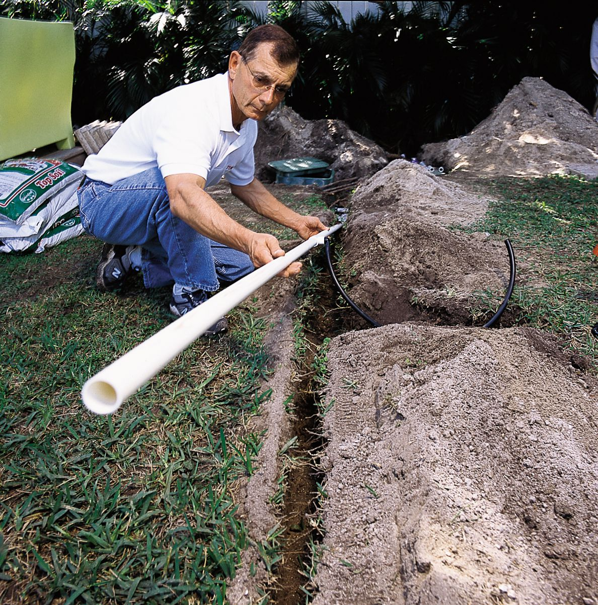 Man Placing Pipes In Trenches For Sprinkler System