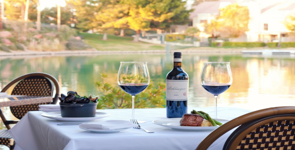 A bottle of wine, two glasses of wine, and more overlooking a lake.