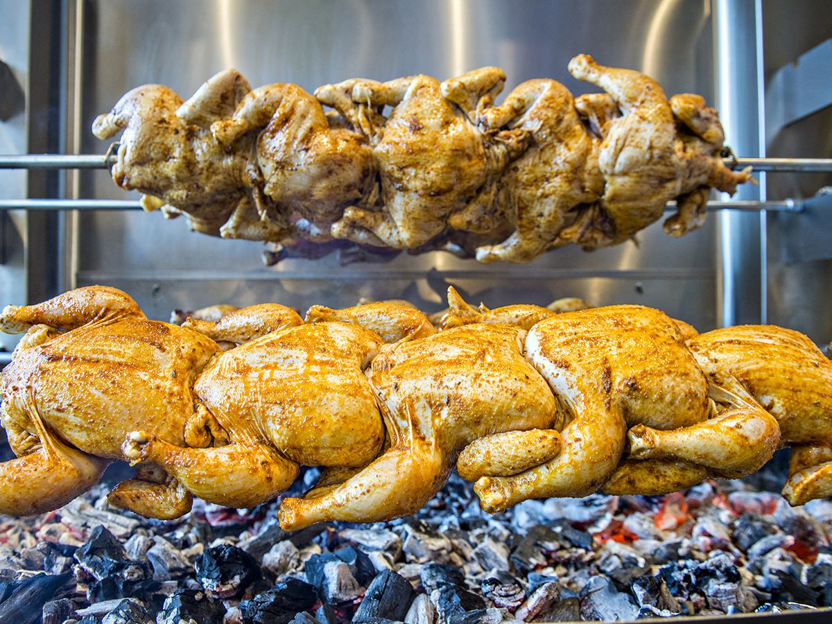 A close-up photo of two line of rotisserie chickens cooking on skewers