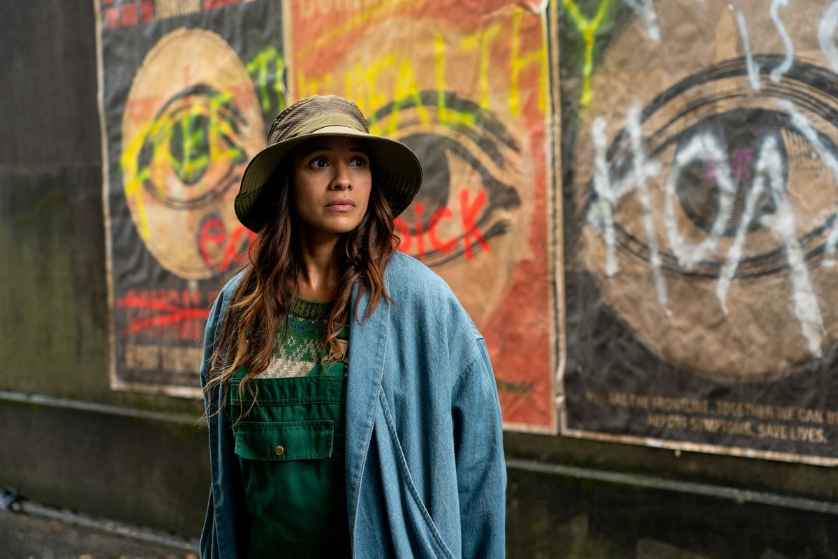 """Dania Ramirez stands in front of a wall covered in graffiti proclaiming """"free the healthy"""" and other slogans about a virus called the Sick, as Aimee in episode 104 of Sweet Tooth."""