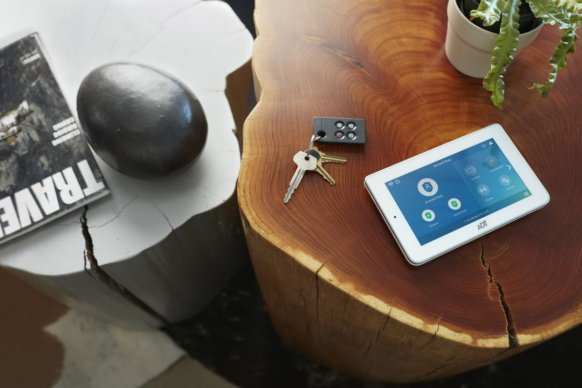 An ADT security touchscreen device sits on a wooden coffee table next to keys, a green plan, and a travel book.
