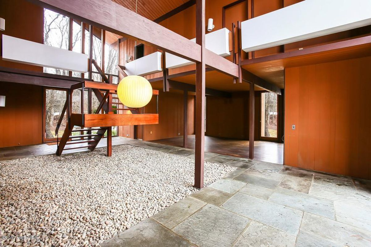 Interior shot of brightly lit double-height foyer with wooden staircase leading up to the second level balcony. Wood panels the walls and the ceiling, and pebbles make up an atrium-like space in the middle.