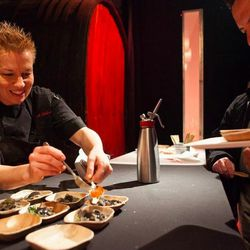 Elizabeth Falkner plating dishes for attendees at the World Market