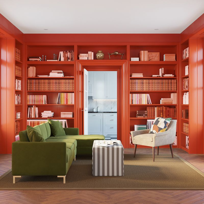 Green sectional sofa, a gray armchair, and gray-and-white striped ottoman sit in a room with coral built-in shelves.