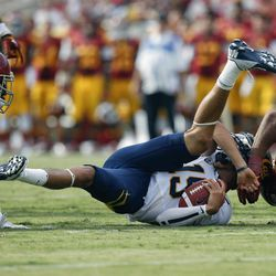 California quarterback Zach Maynard, center, is sacked by Southern California defensive end Wes Horton, right, during the first half of an NCAA college football game in Los Angeles, Saturday, Sept. 22, 2012.