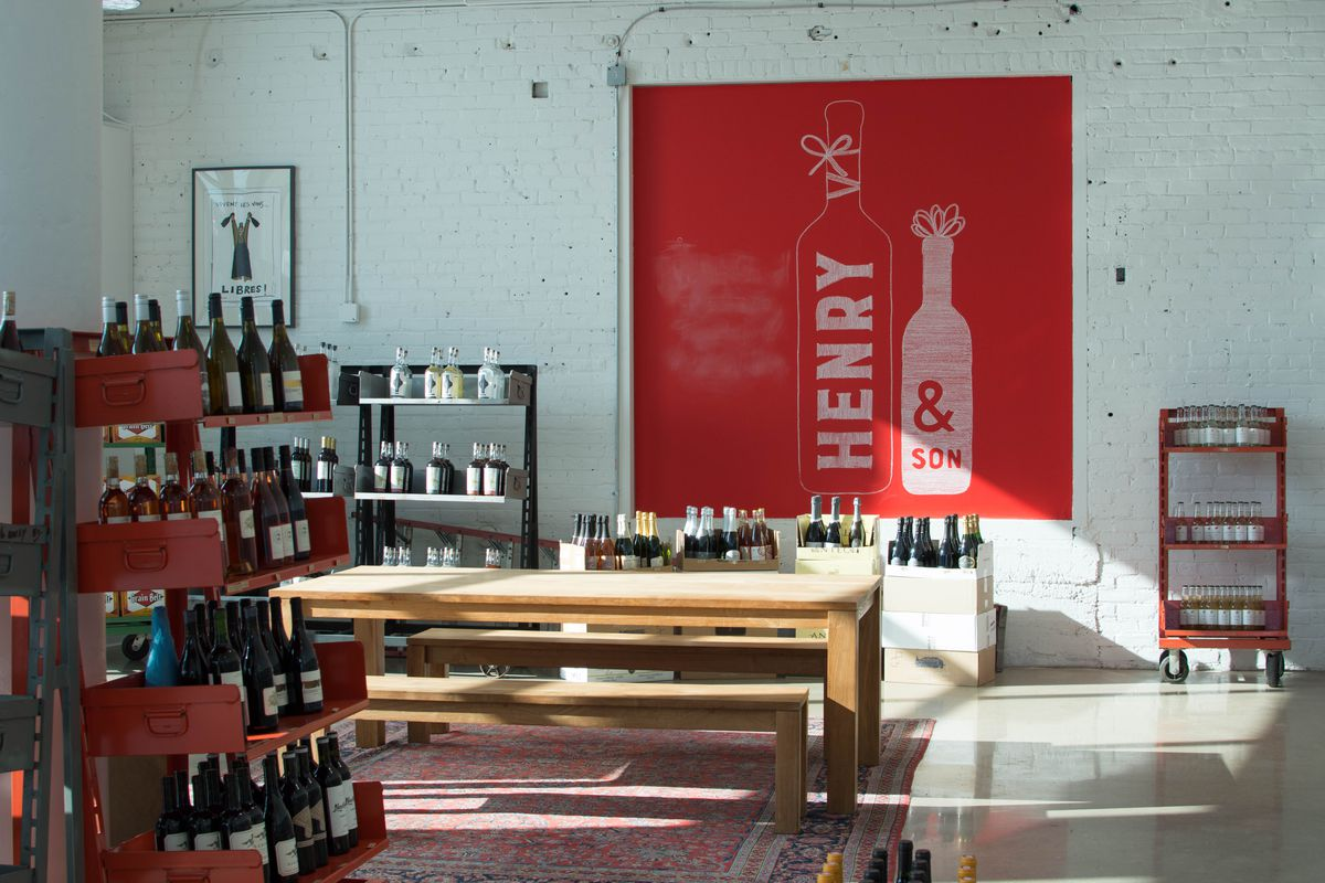 """Inside Henry & Son wine shop with a wide open, white panted industrial room featuring racks of natural wines. A red with white banner is behind the cash wrap that says """"Henry & Son."""""""