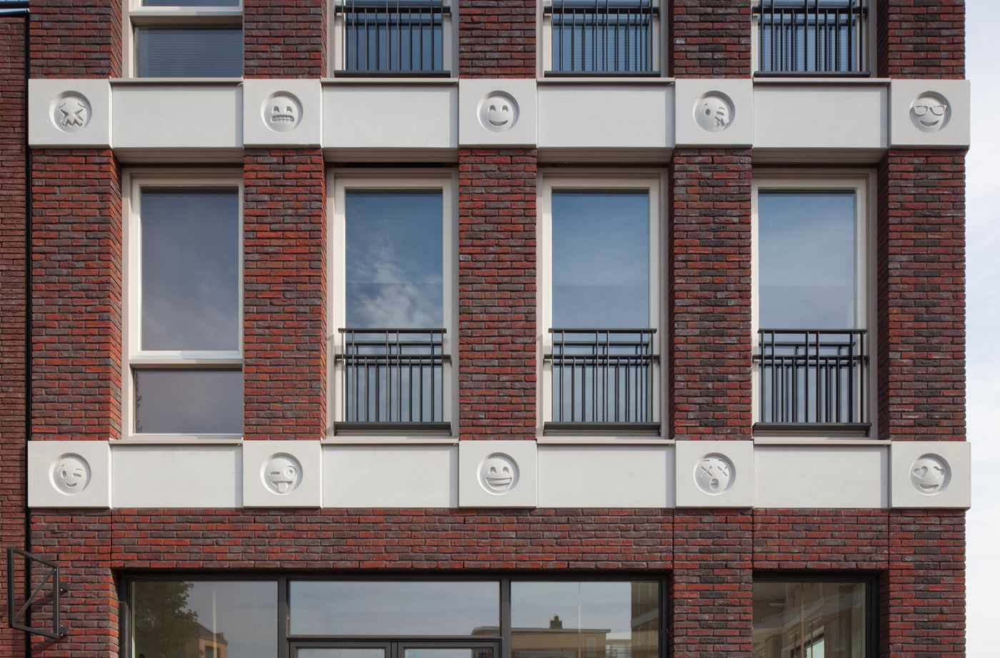 Close up of facade of brick building with face emojis cast in white concrete that run horizontally at the top of each story.