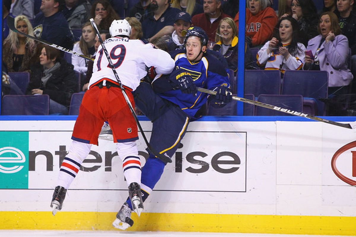 ST. LOUIS, MO - MARCH 7: Nikita Nikitin #64 of the St. Louis Blues is checked into the boards by Ethan Moreau #19 of the Columbus Blue Jackets at the Scottrade Center on March 7, 2011 in St. Louis, Missouri.  (Photo by Dilip Vishwanat/Getty Images)
