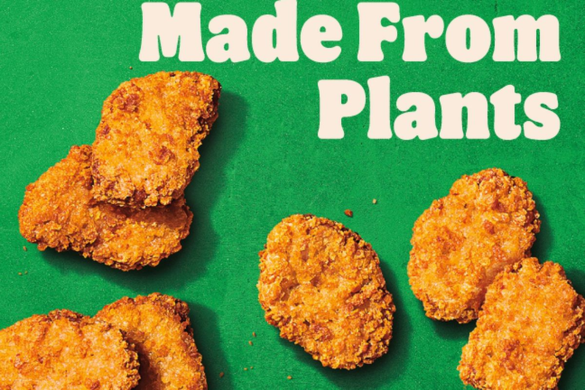 """A promotional poster from Burger King advertises the company's new Impossible nuggets, with the slogan """"Made From Plants"""" printed in white font against a green background."""