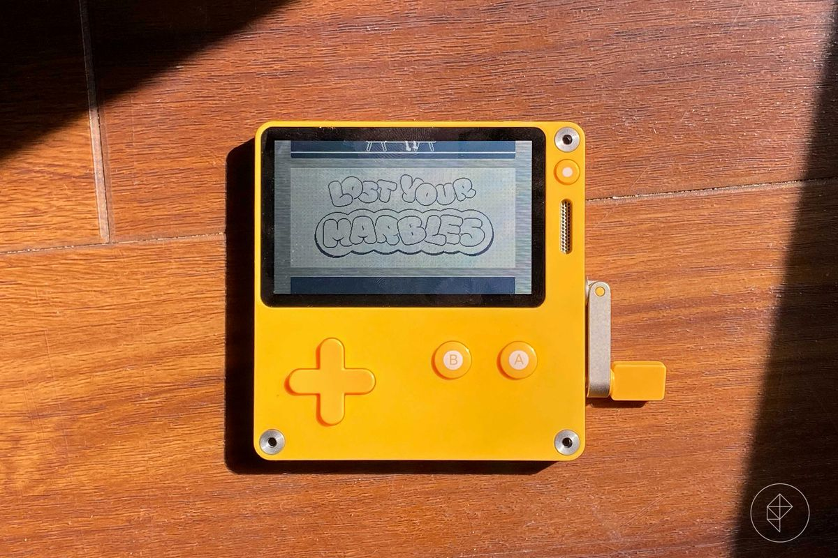 A yellow GameBoy-like device called the Playdate sits in a beam of sunlight on a wooden floor. The bubbly words Lost Your Marbles sit on the screen.