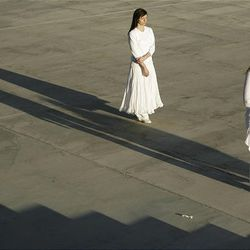 """Performers in Ernesto Pujol's durational art piece """"Awaiting"""" walk near the steps of the state Capitol in Salt Lake City Thursday. The performers, wearing all white, walked from various points in Salt Lake City to convene on the steps of the Capitol, where they walked up and down for 12 hours. Local artists and University of Utah students were involved in the performance."""