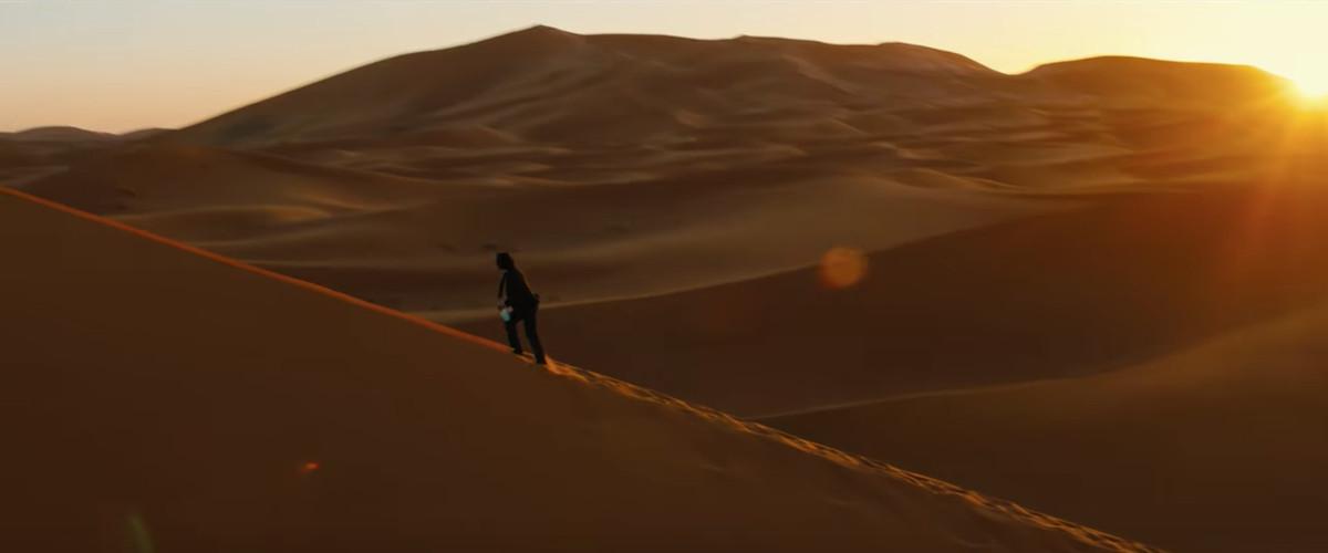 Wide shot of John Wick walking in the desert