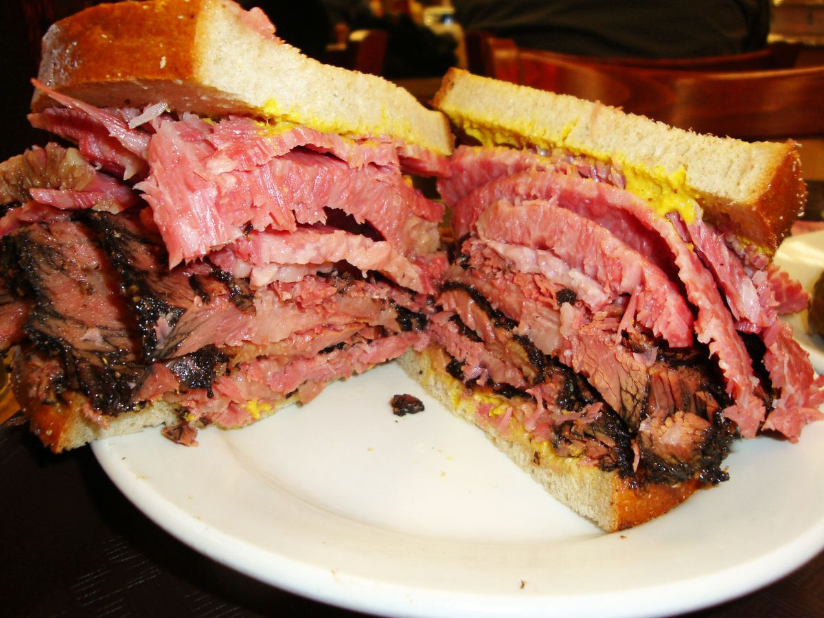 A piled high on rye sandwich bulging with two very pink meats