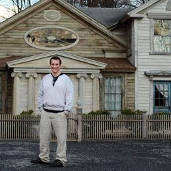 """In this photo taken Feb. 1, 2012, Bronson Pinchot poses for photos in front of the Decker House, one of six properties he owns in Harford, Pa.  Pinchot, best known for his starring role on the 1980's sitcom """"Perfect Strangers,"""" is back on TV with a new show about restoring his historic Pennsylvania homes. The show, """"The Bronson Pinchot Project,"""" premiered this month on the DIY cable network."""