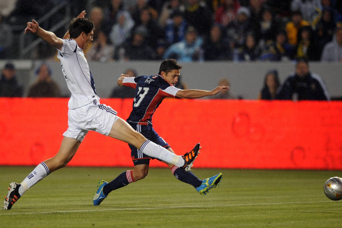 Mar 31, 2012; Carson, CA, USA; New England Revolution forward Ryan Guy (13) attempts a pass defended by Los Angeles Galaxy defenseman Andrew Boyens (29) during the first half at the Home Depot Center. Mandatory Credit: Kelvin Kuo-US PRESSWIRE