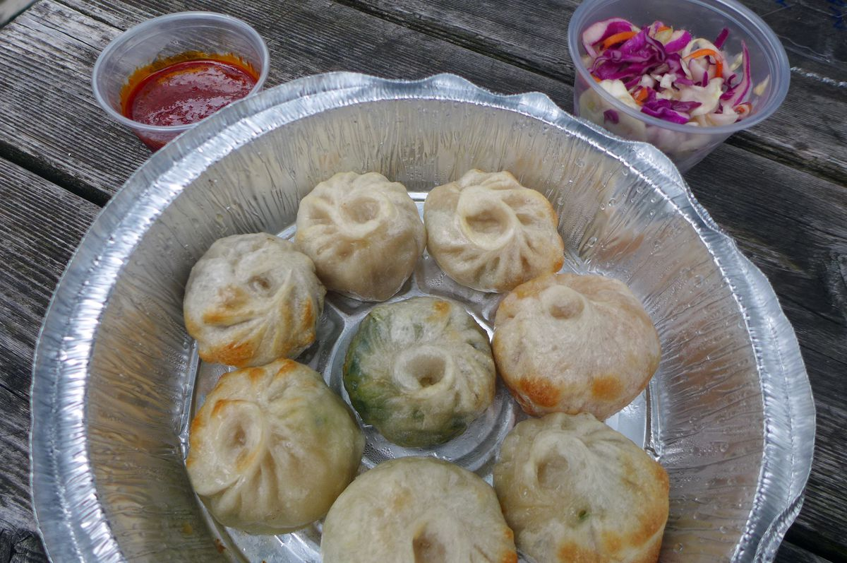 Aluminum carryout container with eight round dumplings, each with a different filling, imparting slightly different colors to the dumplings.
