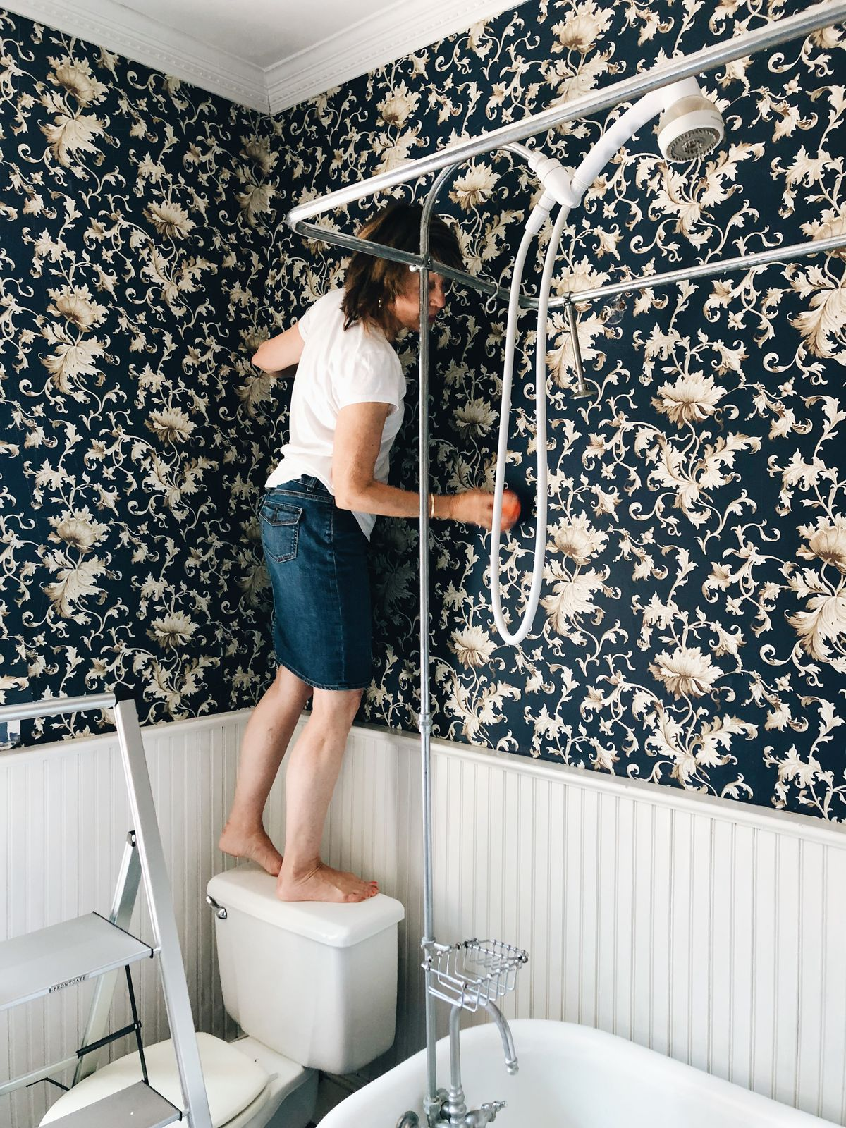 Kelsey Keith's mom removes dark patterned wallpaper from a bathroom wall.