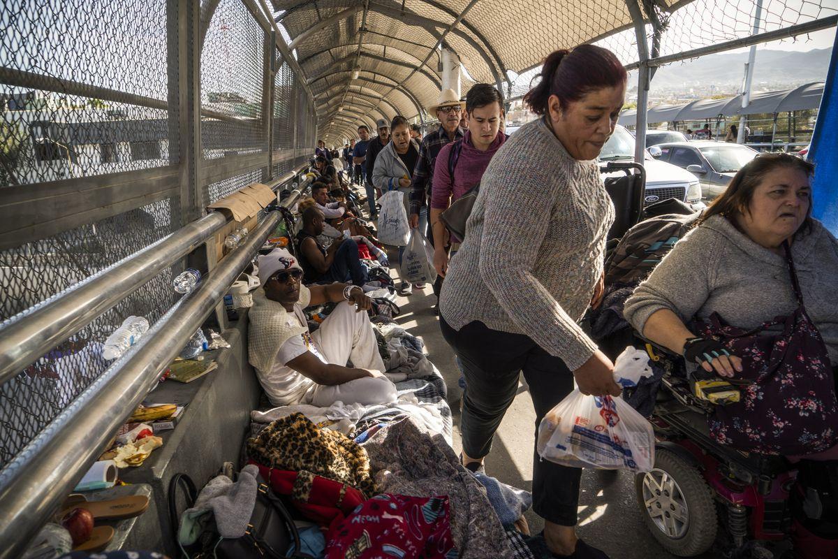 Pedestrians weave through an encampment of migrants occupying the Paso Del Norte Bridge on November 4, 2018 in El Paso, Texas.