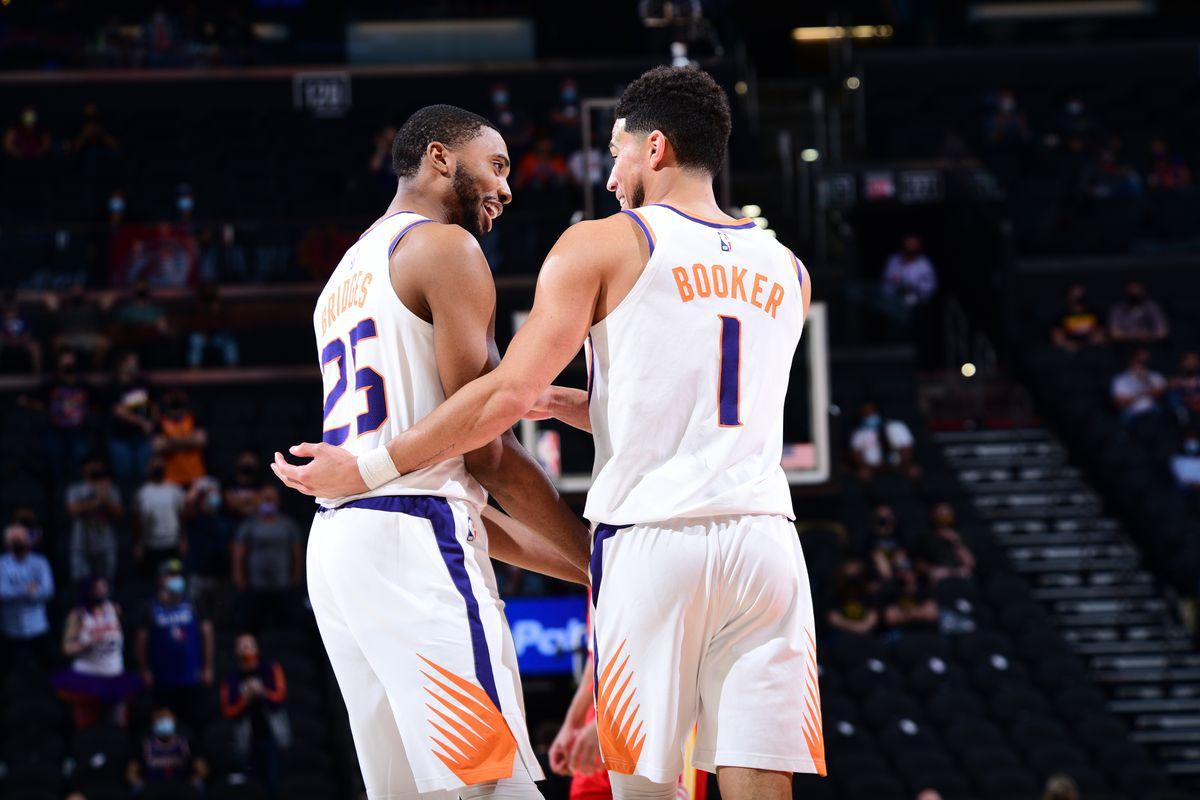 Mikal Bridges of the Phoenix Suns talks with Devin Booker of the Phoenix Suns during the game against the Atlanta Hawks on March 30, 2021 at Phoenix Suns Arena in Phoenix, Arizona.