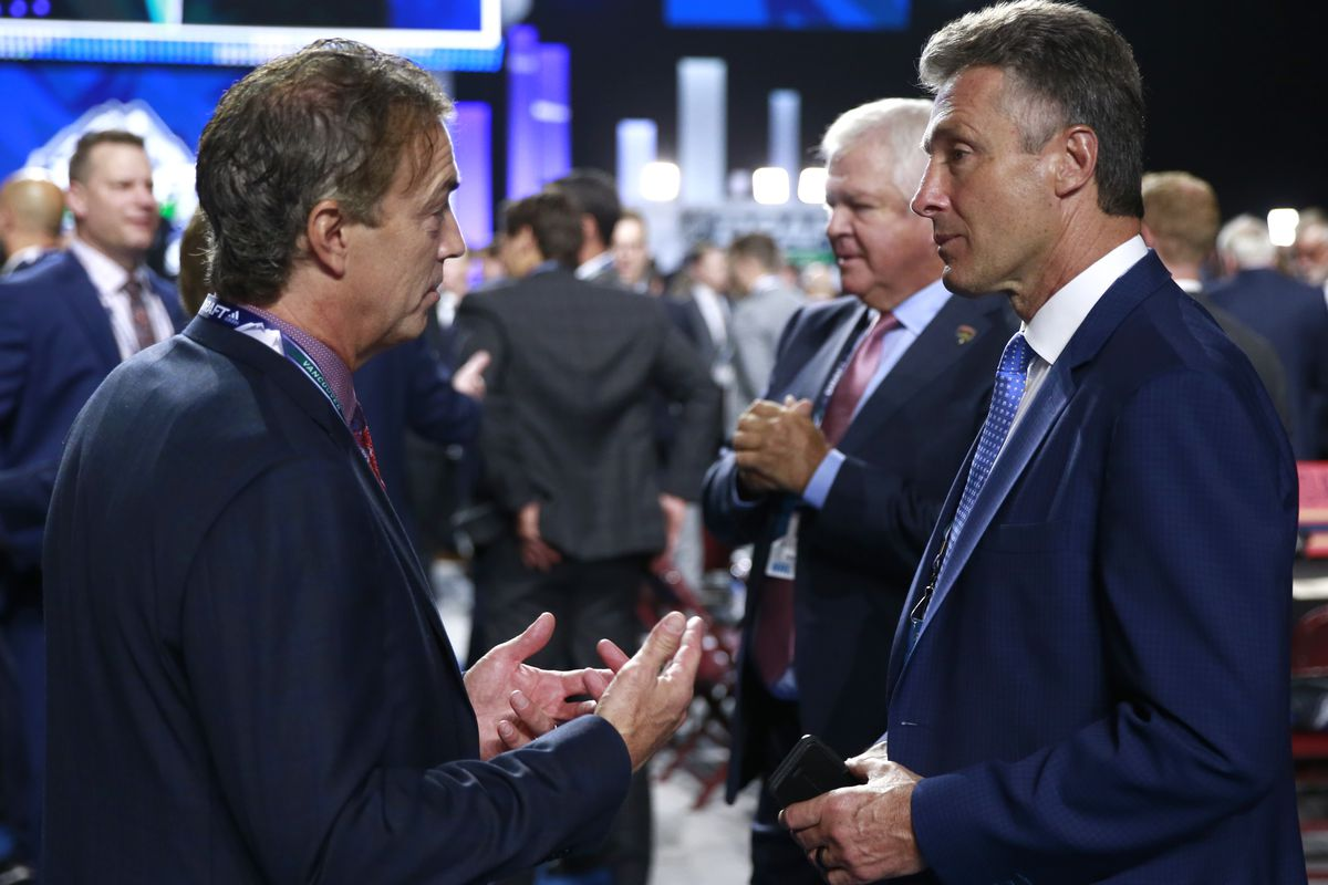 VANCOUVER, BRITISH COLUMBIA - JUNE 21: General managers Joe Sakic of the Colorado Avalanche (L) and Doug Wilson of the San Jose Sharks talk on the draft floor during the first round of the 2019 NHL Draft at Rogers Arena on June 21, 2019 in Vancouver, Canada.