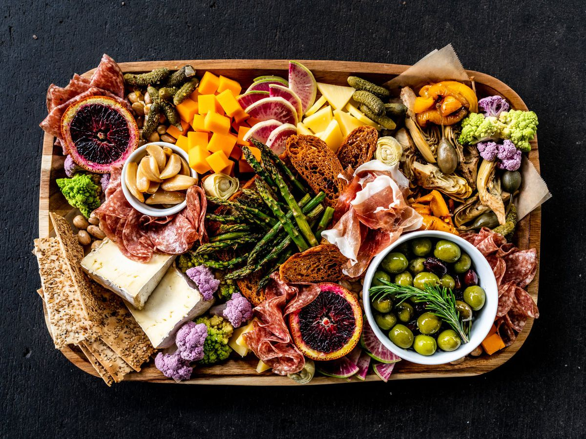 An extremely colorful array of sliced meats, cheese, pickled vegetables, fruits, and crackers
