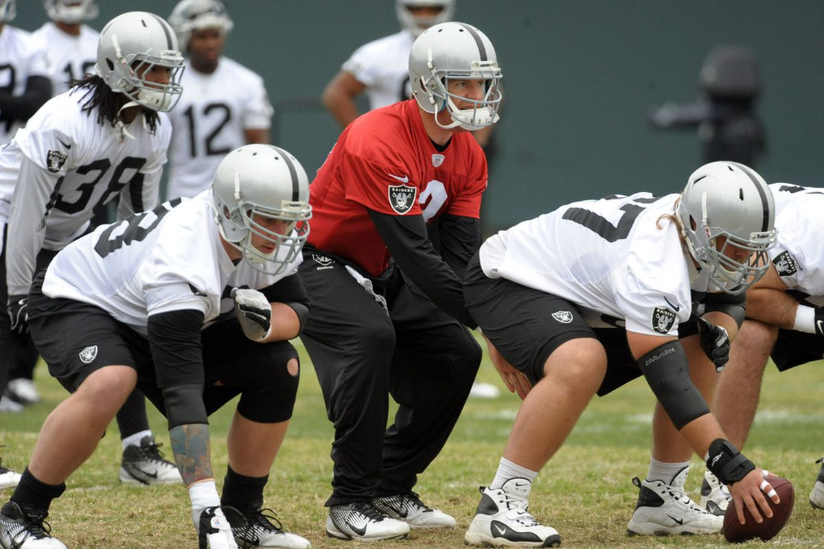 Oakland Raiders quarterback Carson Palmer (3) takes the snap from Alex Parsons (67) at organized team activities at the Raiders practice facility.