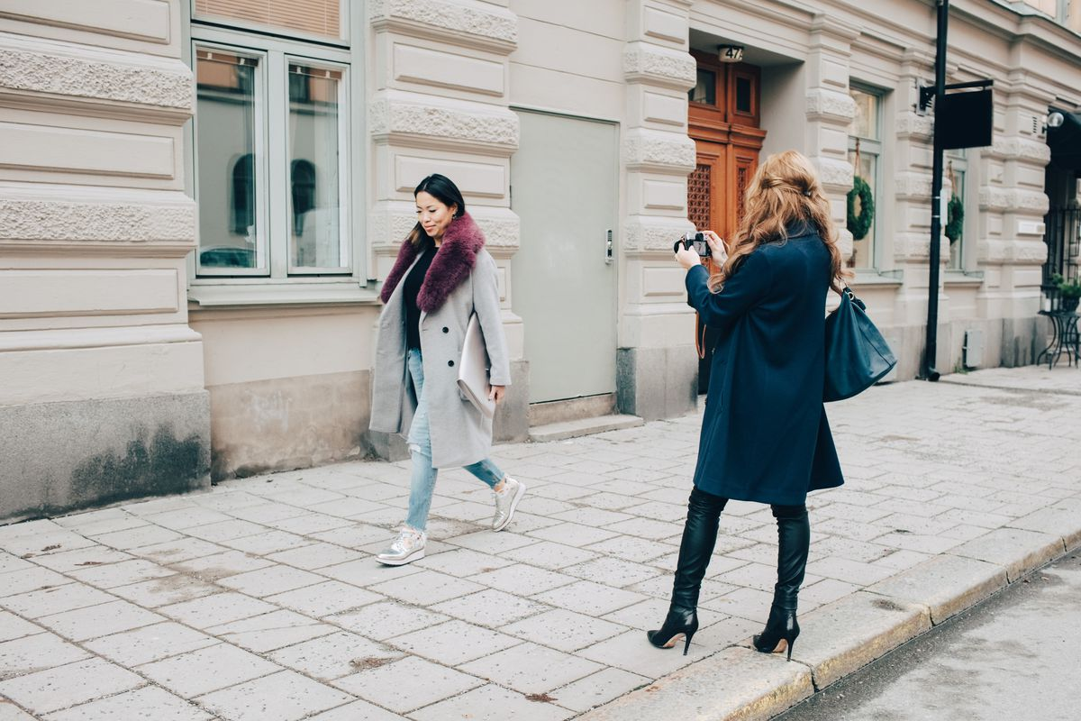 A woman takes a picture of another woman walking past.
