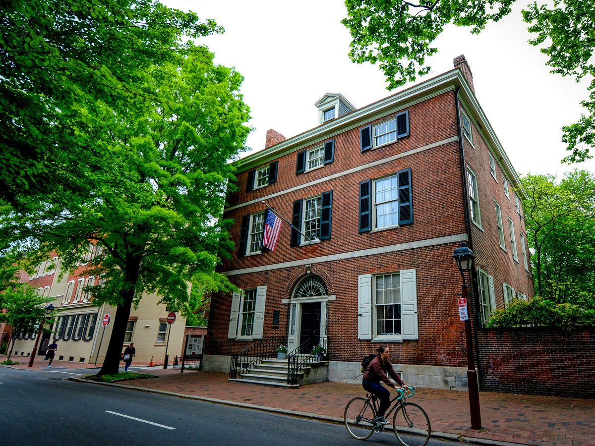 The exterior of the Physick House. The facade is red brick. There is a person riding a bicycle in the street in front.
