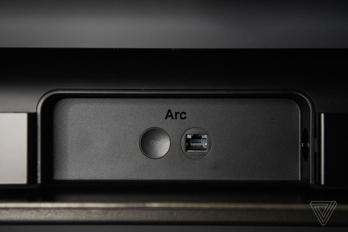 A aspect shot of the support of the Sonos Arc, showing the ethernet jack and vitality button.