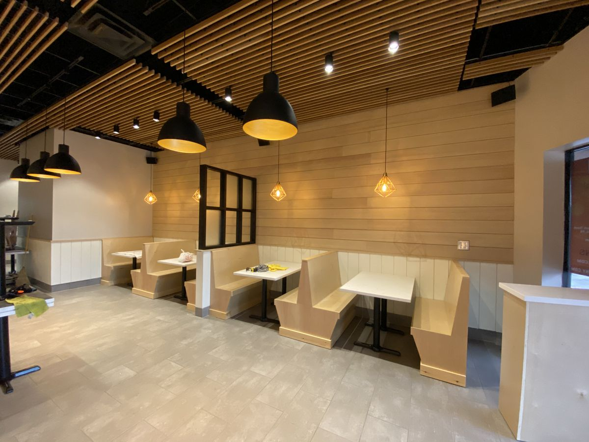 A view of three blonde wood booths with tables inside Pho Ga Tony Tony