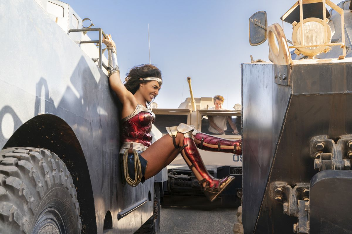Wonder Woman pushes two cars away from each other as Steve Trevor follows her with a tank in Wonder Woman 1984