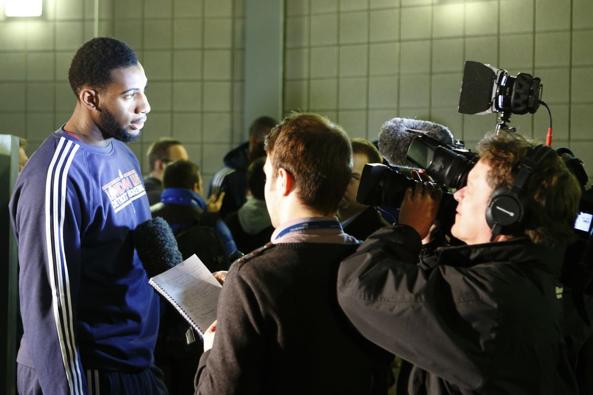 Andre Drummond surrounded by a bunch of cocked dictaphones.