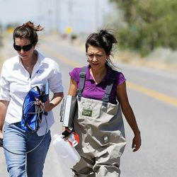 Calah Worthen, left, and Suzan Tahir, environmental scientists for the Utah Department of Environmental Quality's water quality division, walk to the Jordan River to take water samples in North Salt Lake on Monday, July 18, 2016.