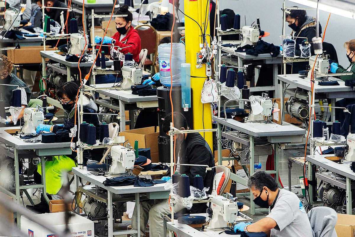 Workers in an industrial sewing room sit at sewing machines.