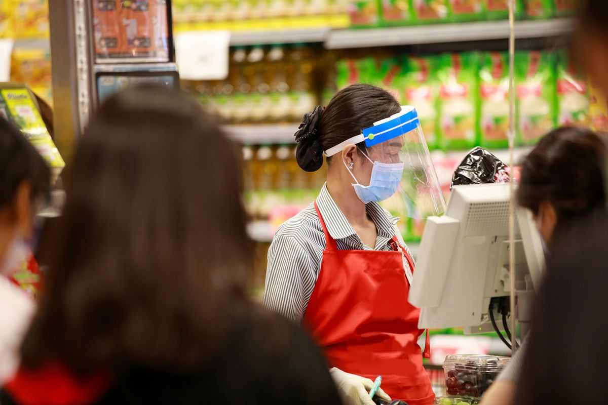 A female cashier in medical protective mask and face shield with a red apron working at supermarket.