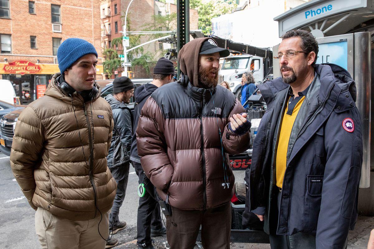 Benny Safdie, Josh Safdie, Adam Sandler stand on set in new york city