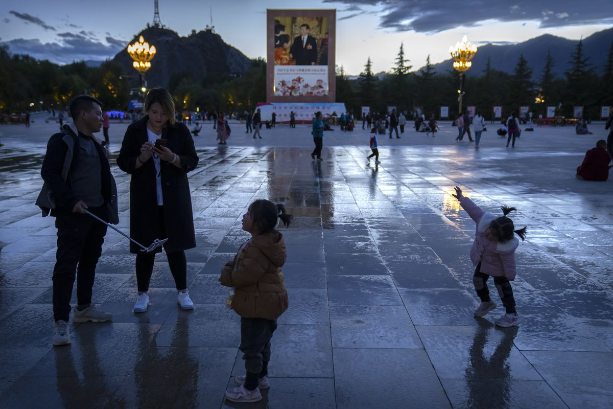 Tourists stand near a large mural of Chinese President Xi Jinping in a square near the Potala Palace in Lhasa, western China's Tibet Autonomous Region.