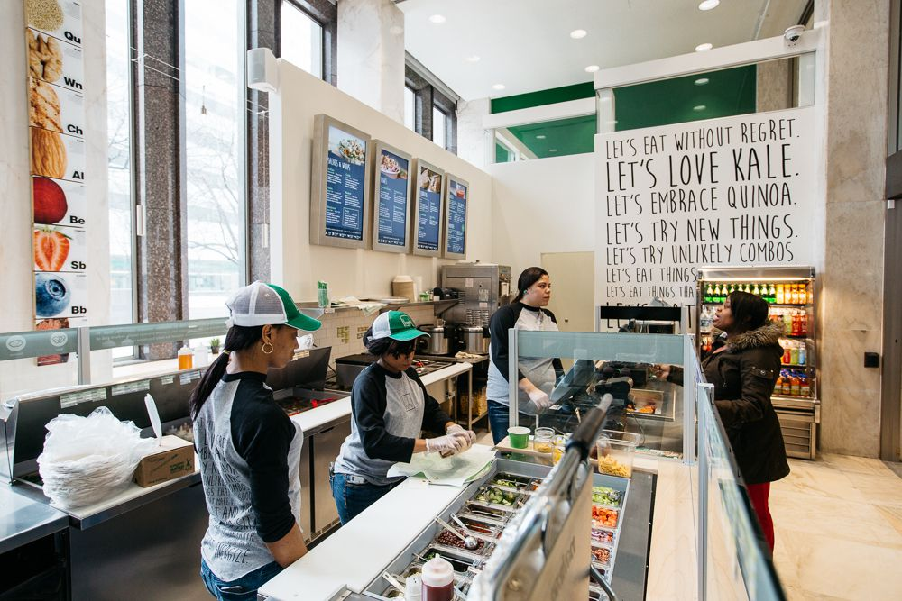 three workers behind the counter at freshii wearing black and white baseball-style shirts and hats with a green bill