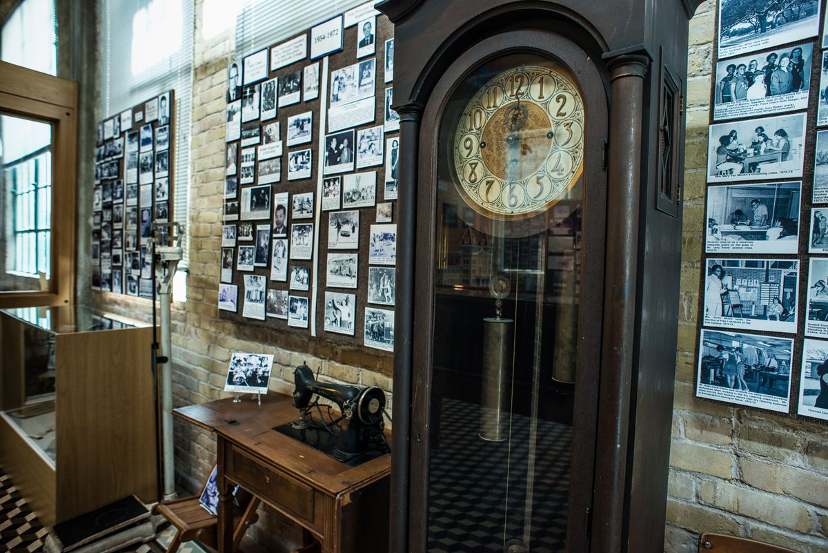 Interior of brick building with antique grandfather clock, sewing machine, lots of black and white photos on walls, display case