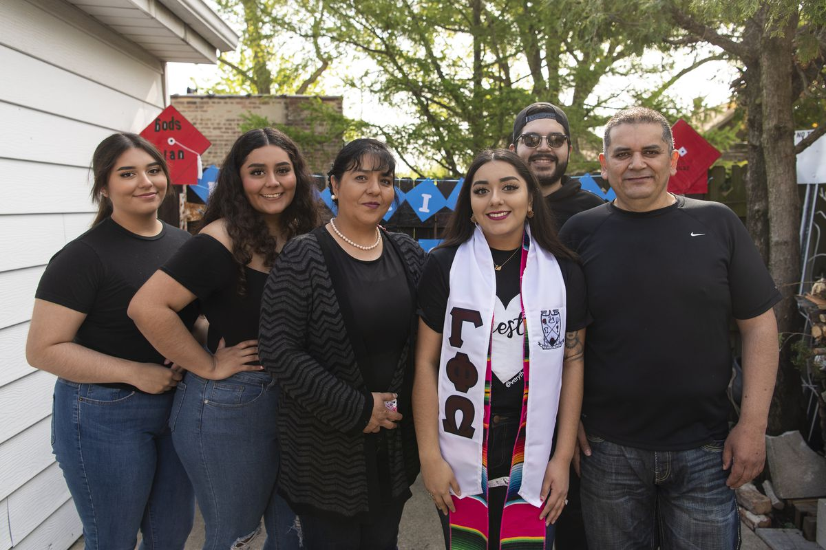 Edith Mendez poses in her backyard with her family after her virtual commencement ceremony from UIC Saturday.