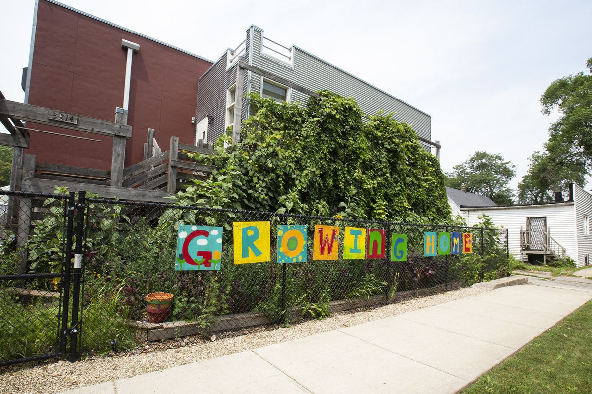 """A fence in front of a building with leaves growing and a colorful sign reading """"Growing Home."""""""