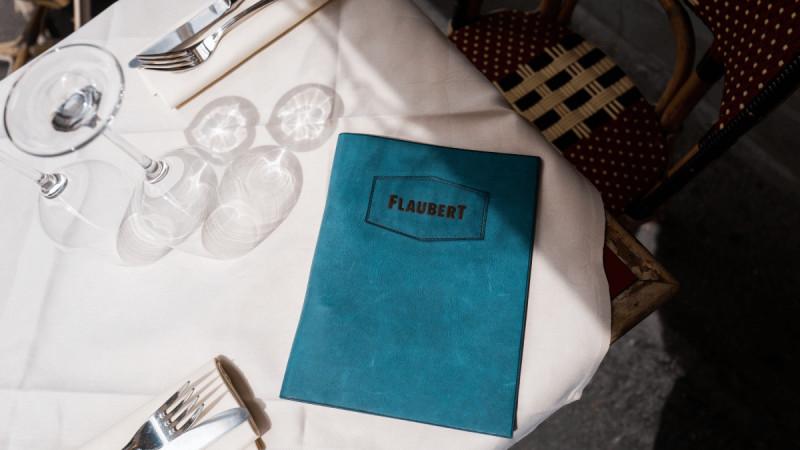 A blue velvet menu on a sunlit table beside place settings