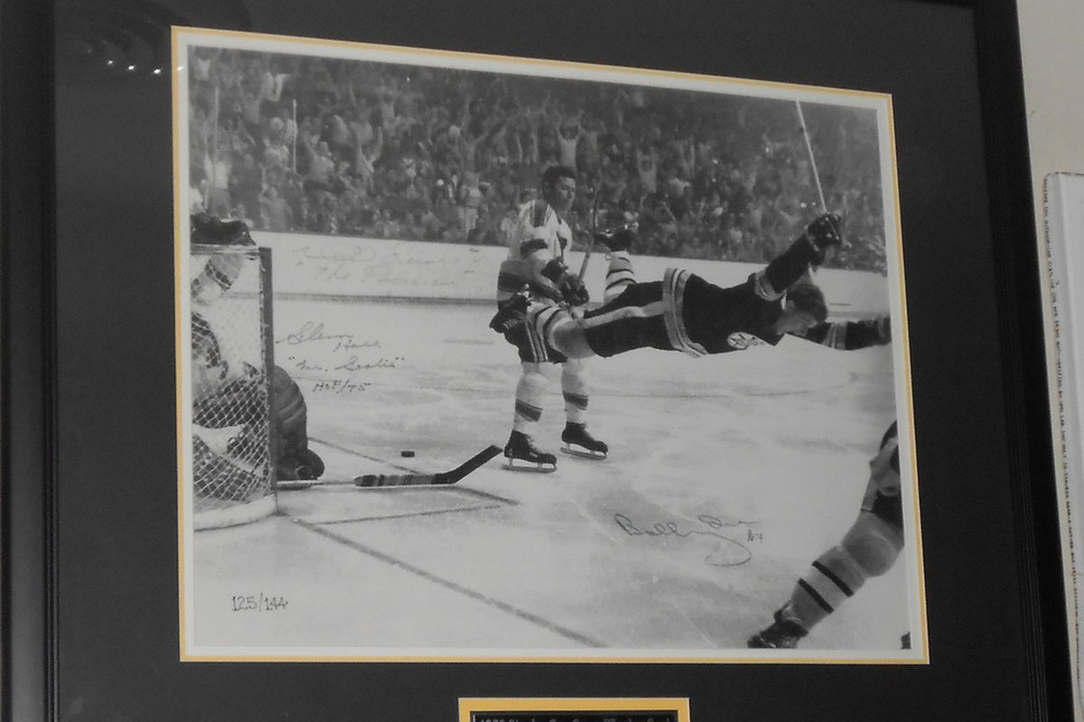 """""""The Goal"""" photograph, individually signed by Glenn Hall, Noel Picard and Bobby Orr. Signed pucks from each at bottom of picture."""