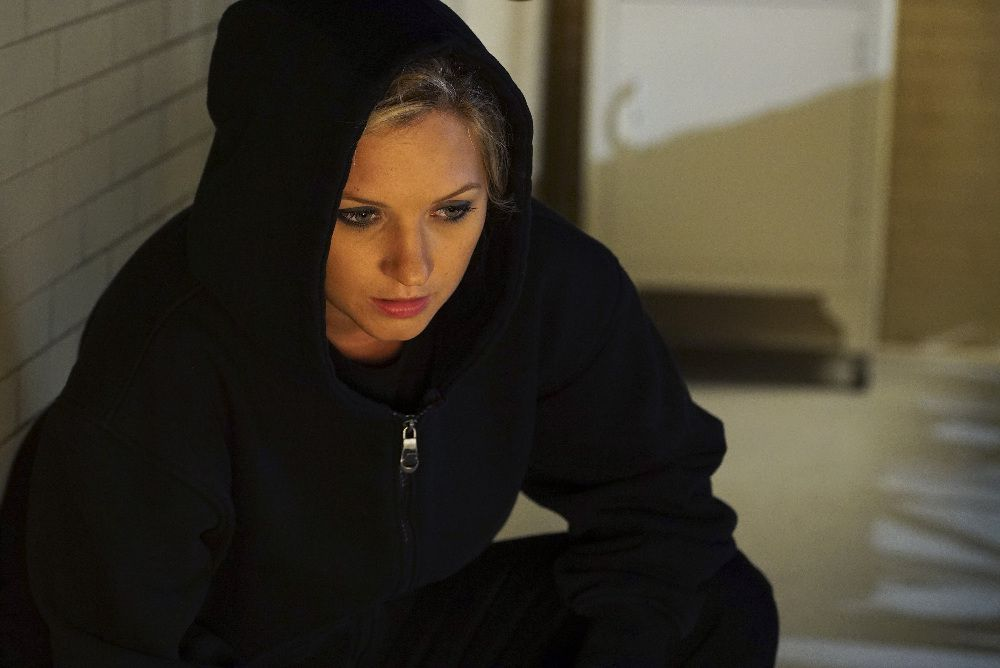 Vanessa Ray crouching and wearing a black hoodie as CeCe Drake/Charlotte DiLaurentis