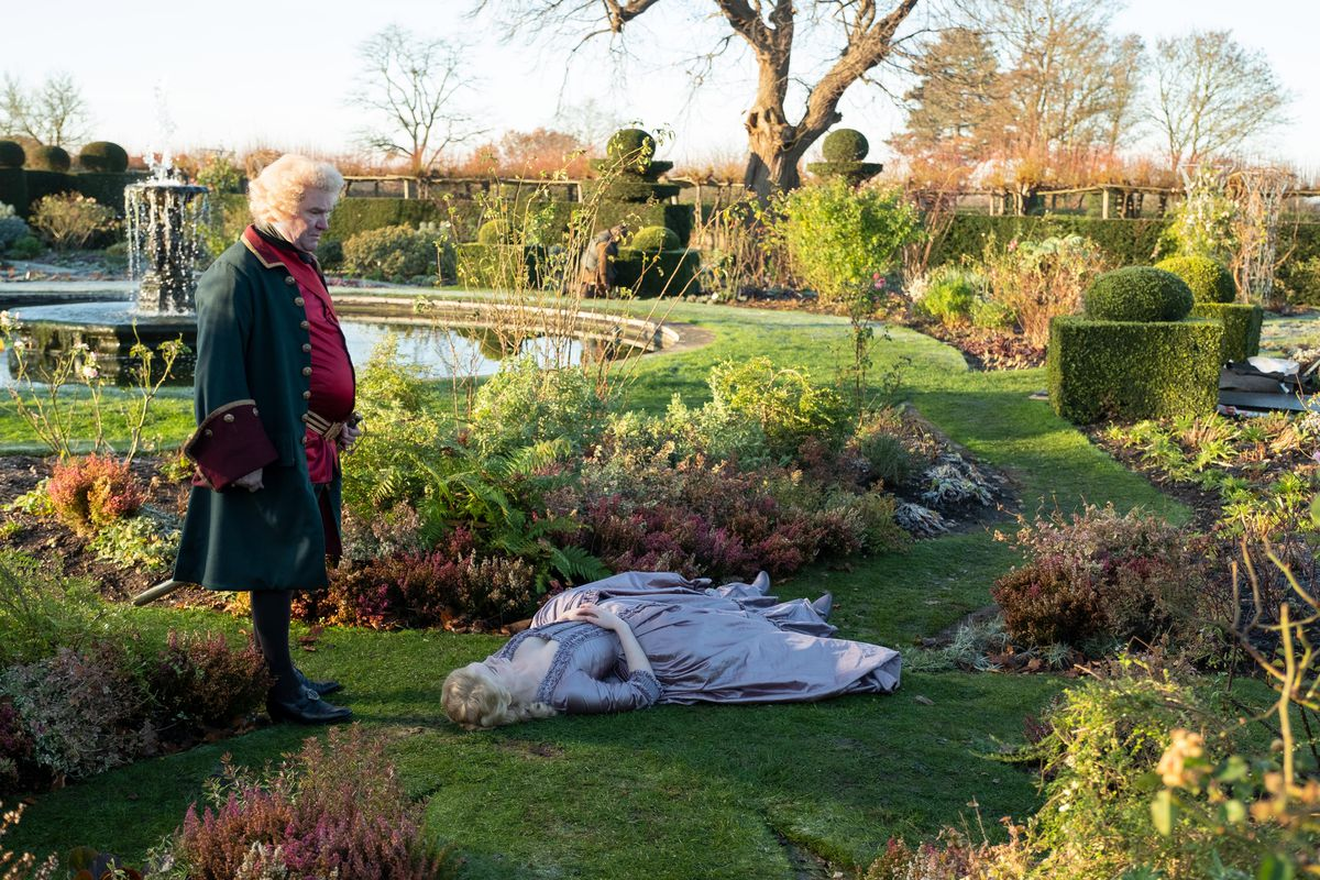 Catherine the Great flops on her back in an elaborate palace garden as a dubious courtier looks on.