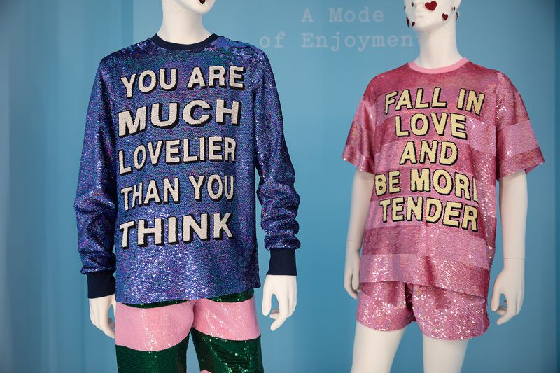 "Two glittery shirts, one of which says ""You are much lovelier than you think"" and the other ""Fall in love and be more tender."""