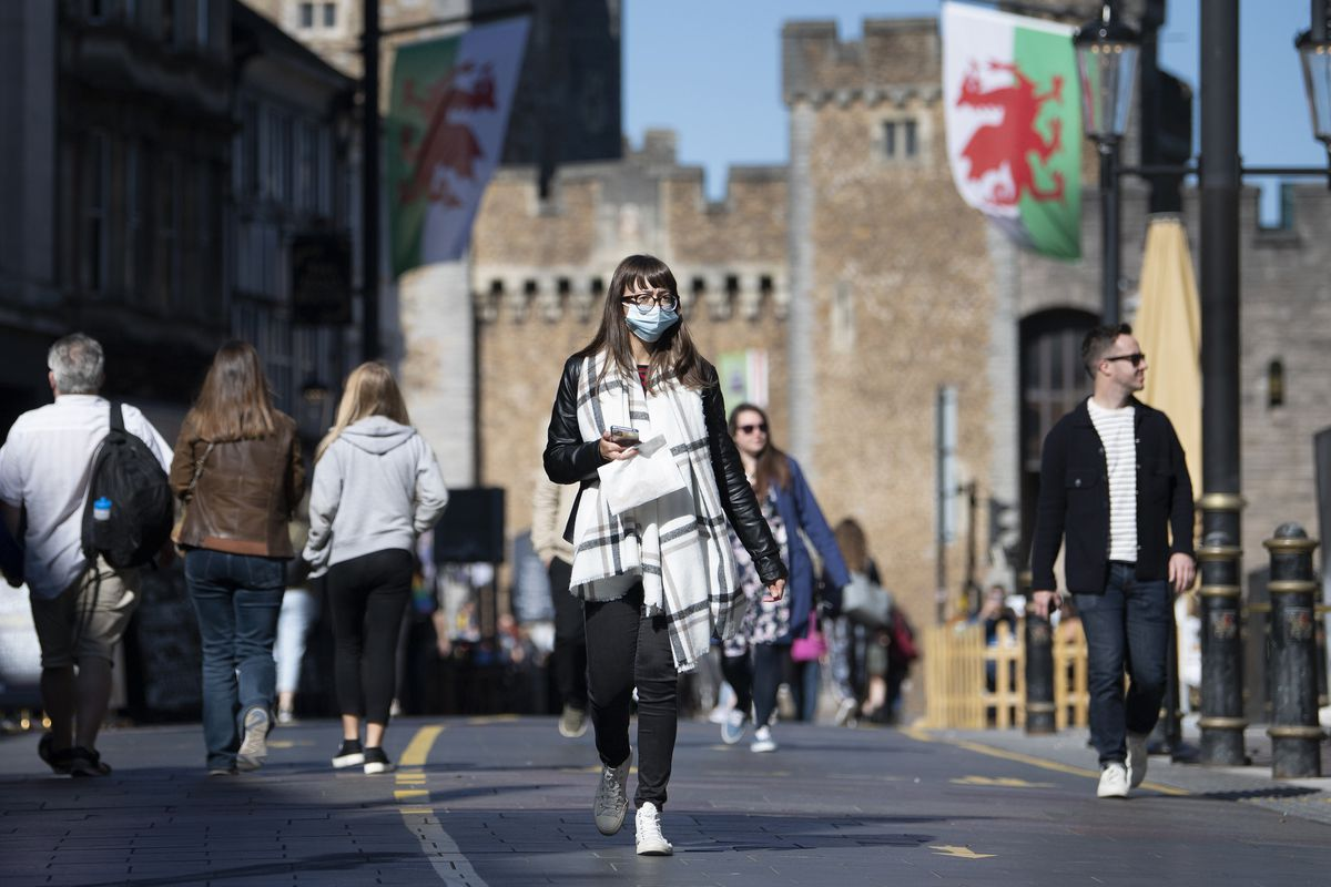 A person walking on a street in front of Cardiff Castle, Wales.