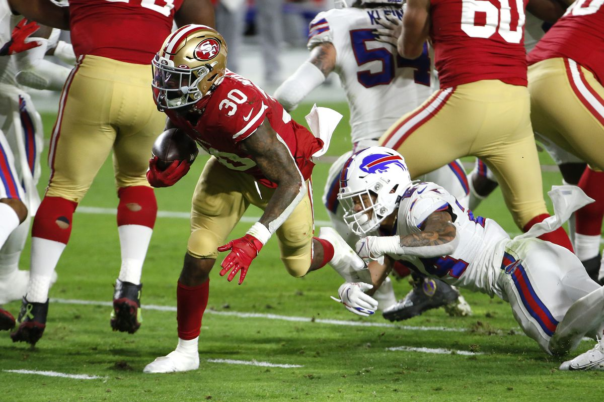 Running back Jeff Wilson #30 of the San Francisco 49ers rushes ahead of cornerback Taron Johnson #24 of the Buffalo Bills during the first quarter at State Farm Stadium on December 07, 2020 in Glendale, Arizona.