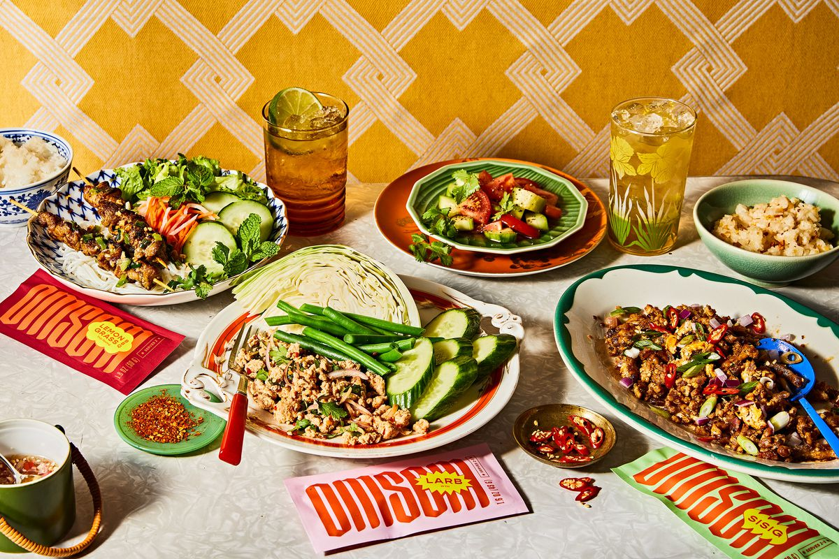 Five plates of food and two drinks sit on a table, alongside smaller bowls of dipping sauces