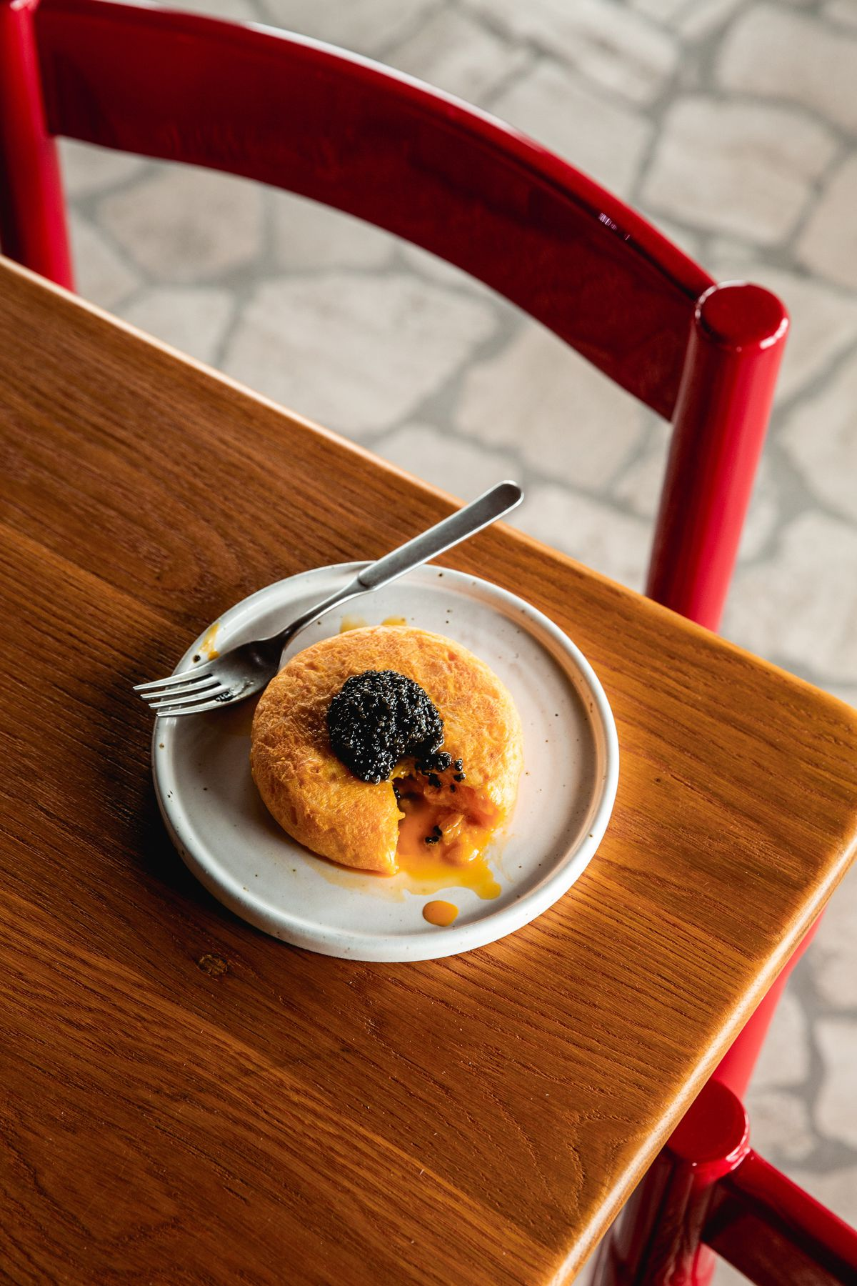 Tortilla with caviar on a wooden table with a red chair at Decimo, the new King's Cross restaurant by chef Peter Sanchez Iglesias at The Standard Hotel London